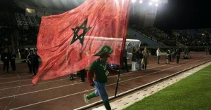 """A supporter runs with a Moroccan flag during the sixth """"Match against Poverty"""" in Fes"""