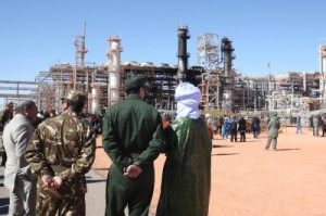 In this file photo, Algerian soldiers and officials stand in front of the In Amenas gas plant that former Algerian soldier Mokhtar Belmokhtar's militants assaulted in 2013. (Associated Press)