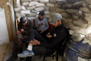 Free Syrian Army fighters use their smartphones behind sandbags in the Al-Maysar neighbourhood of Aleppo May 3, 2014. REUTERS/Jalal Al-Mamo (SYRIA - Tags: CIVIL UNREST MILITARY POLITICS SOCIETY CONFLICT) - RTR3NNM2